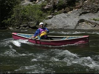 Surfing a canoe in whitewater